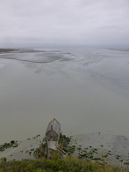 Chapelle devant les flots gris de la baie