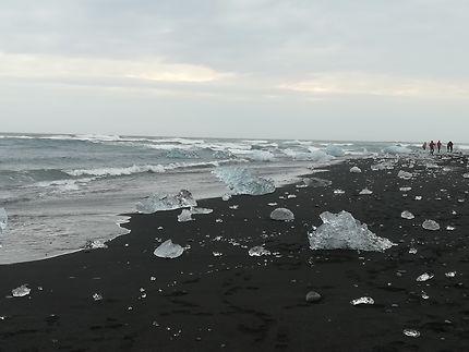 Plage de sable noir avec des morceaux d'icebergs