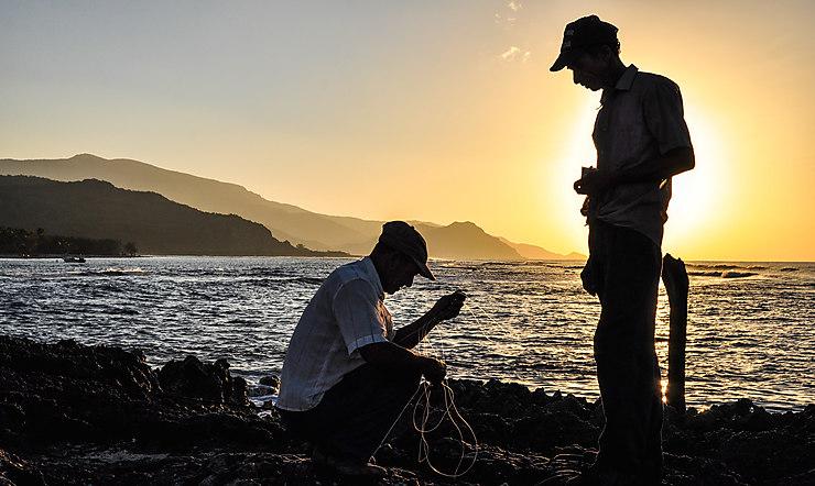 Des pêcheurs entretiennent leurs filets à Playa Cazonal