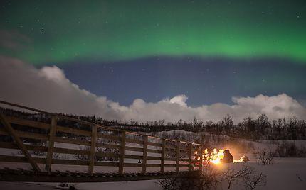 Feu de camp sous les aurores boréales